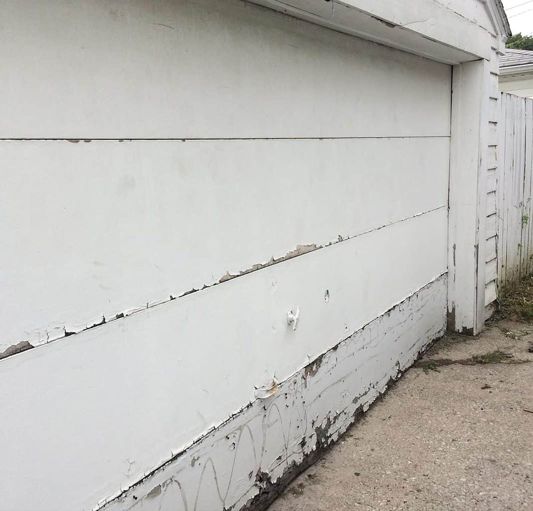 Garage door with a rotted bottom panel